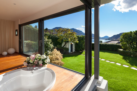 contemporary: Comfortable bathroom with round bathtub, windows overlooking the garden Stock Photo