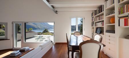 case moderne: Gli interni, soggiorno di un soppalco, tavolo in legno e divano bianco