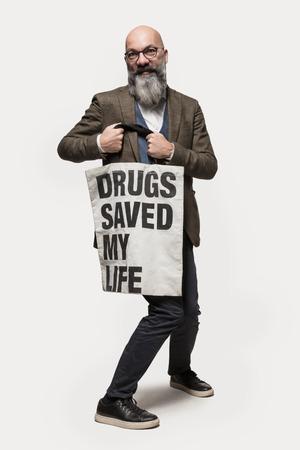 manifest: man shows a bag with slogan, studio portrait Stock Photo