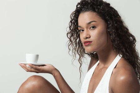 Young woman holds in the palm of  hand a cup of coffee,  portrait in studio