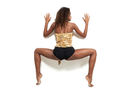 contortionist: Performance of a young brazilian dancer with a elegant bodysuit, rear view, portrait in studio