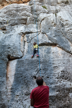 dangle: Little girl climbing on a limestone wall, rock on the background