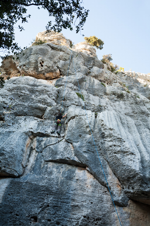 dangle: Boy climbing on a limestone wall, rock and sky on the background Stock Photo