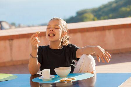 niña comiendo: Little girl having breakfast with a cup of milk and cookies, outdoors Foto de archivo