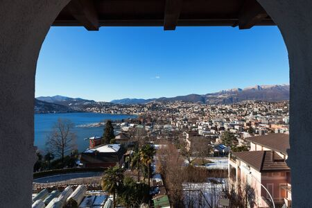 urban landscapes: Panoramic view of Lugano city and the mountains in background, Ticino, Switzerland Stock Photo