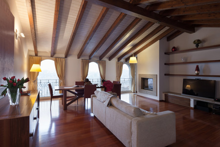 divan: Comfortable, loft, living room with a divan and dining table, wooden floor Foto de archivo