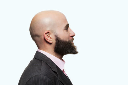head profile: Young bald man with a beard wearing a stylish jacket, side view