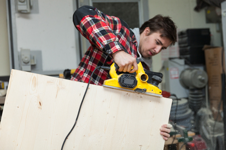 Young carpenter in his workshop working a wooden plank Stock Photo