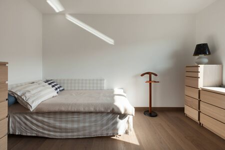 interior walls: Apartment interior, simple bedroom with wooden floor and white walls Stock Photo