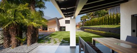 cielos abiertos: Porche de villa moderna con vistas al jardín
