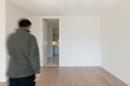 Man seen from behind walks into an empty room