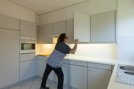 Bizarre man looking for something in an empty kitchen