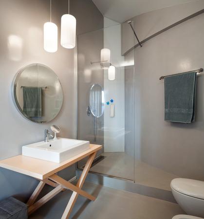ラウンド ミラー付きモダンな浴室の高級アパート
