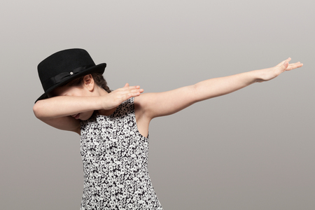 Girl with black hat making Dab, isolated on gray background Stok Fotoğraf