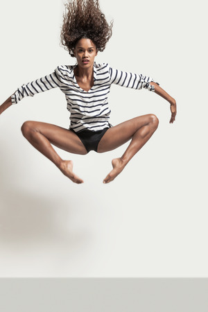 Performance of a young brazilian dancer with a striped shirt, portrait in studio Stock Photo