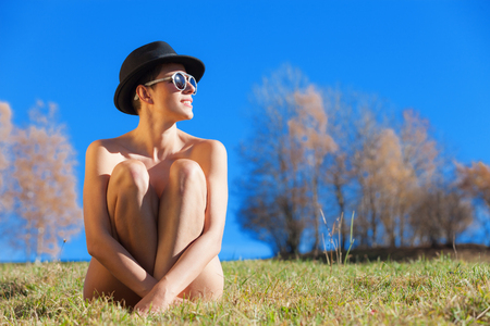 portrait of naked girl with hat and sunglasses, outdoors Archivio Fotografico