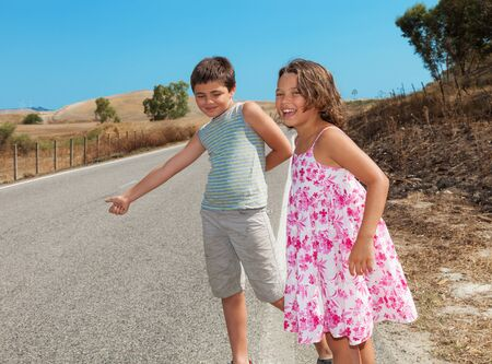2 way: two children  hitchhiking along the street, portrait