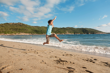 young boy playing running and jumping on the beach