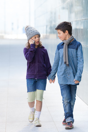 two kids walking in the city, casual clothing, outdoors