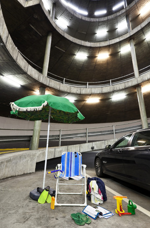 beach umbrella with deckchairs in a parking garage