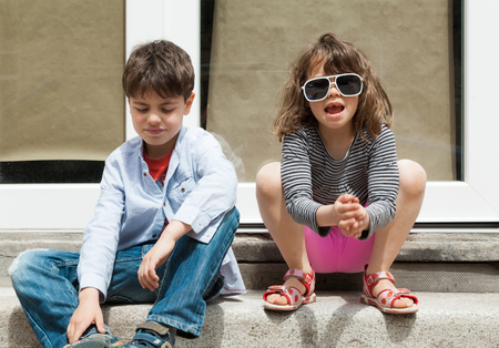 portrait of two children sitting on the sidewalk