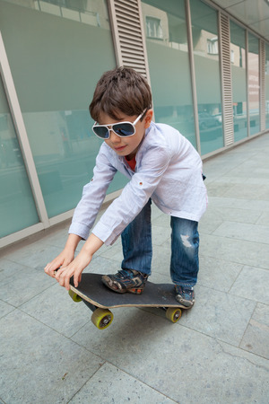 portrait of little boy with sunglasses on the skate, external Archivio Fotografico