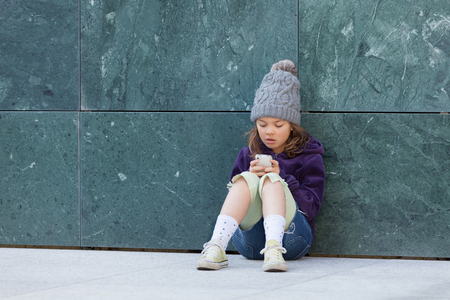 Bambina seduta con il suo smartphone, ritratto