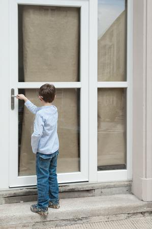 portrait of little boy on the door, rear view