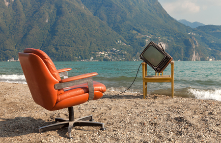 vintage decor on the lake shore, armchair and television Stock Photo