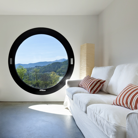 beautiful modern house in cement ,room with large porthole Stock Photo