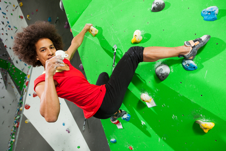 portrait of woman on artificial exercise climbing wall