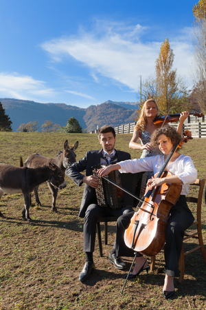 acordeon: Retrato de tres jóvenes músicos, escena en una granja Foto de archivo