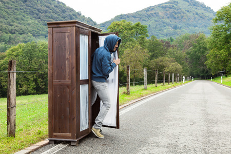 furtive: wooden wardrobe abandoned on a mountain road