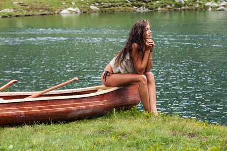 Beautiful young girl sitting over a wooden canoe