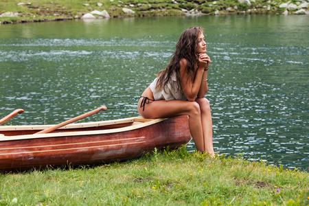 Mooie jonge meisjeszitting over een houten kano