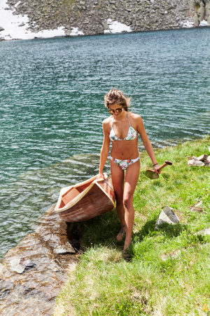 Young girl with a beautiful wooden canoe in the middle of nature, near a lake in Switzerland Stockfoto