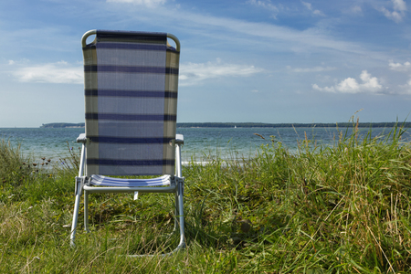 There is only one chair on the deserted beach of northern Europe Archivio Fotografico