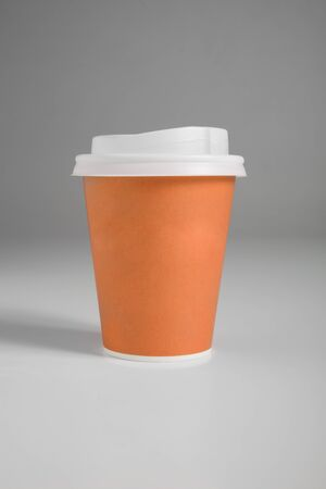 Paper cups on gray background, colored