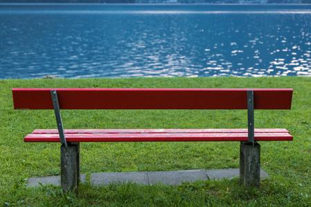 Panchina rossa sulla riva del lago. Tranquillo, calmo