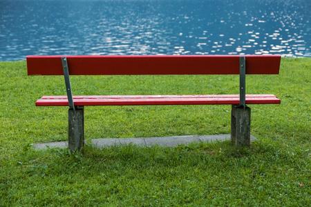 Red bench at lake shore. Peaceful Archivio Fotografico