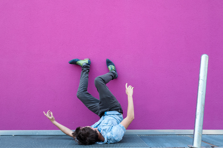 Young man fall on grill. Fuchsia background Stock Photo