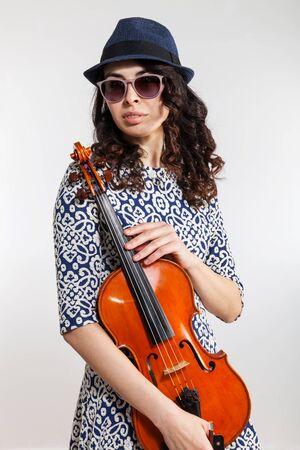 Junger schöner Musiker, der in der Hand im Studio auf weißem Hintergrund mit Viola aufwirft