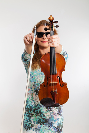 Young blond woman posing in studio with white background. He is a violinist Standard-Bild