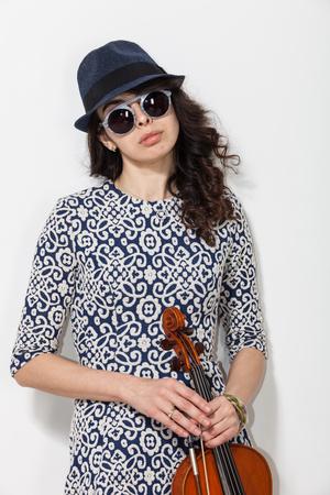 Giovane donna con gli occhiali scuri e un violino in mano