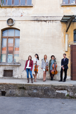 Musical band posing in front of an exterior wall