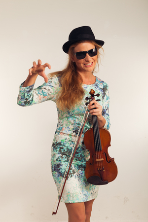 violinista: Young blond woman posing in studio with white background. He is a violinist Foto de archivo