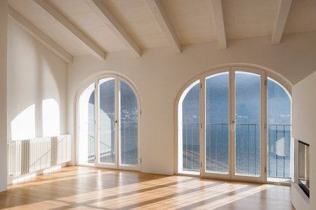 Empty room with large window overlooking the lake. Antique beams on the ceiling of a renovated apartment