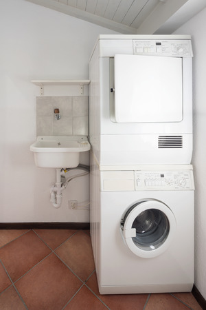 Laundry with washer and dryer stacked on top of each other.