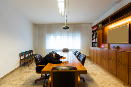 Lonely man in the meeting room is sleeping with his head on the table Archivio Fotografico