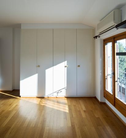 Wardrobe in empty space, parquet floor
